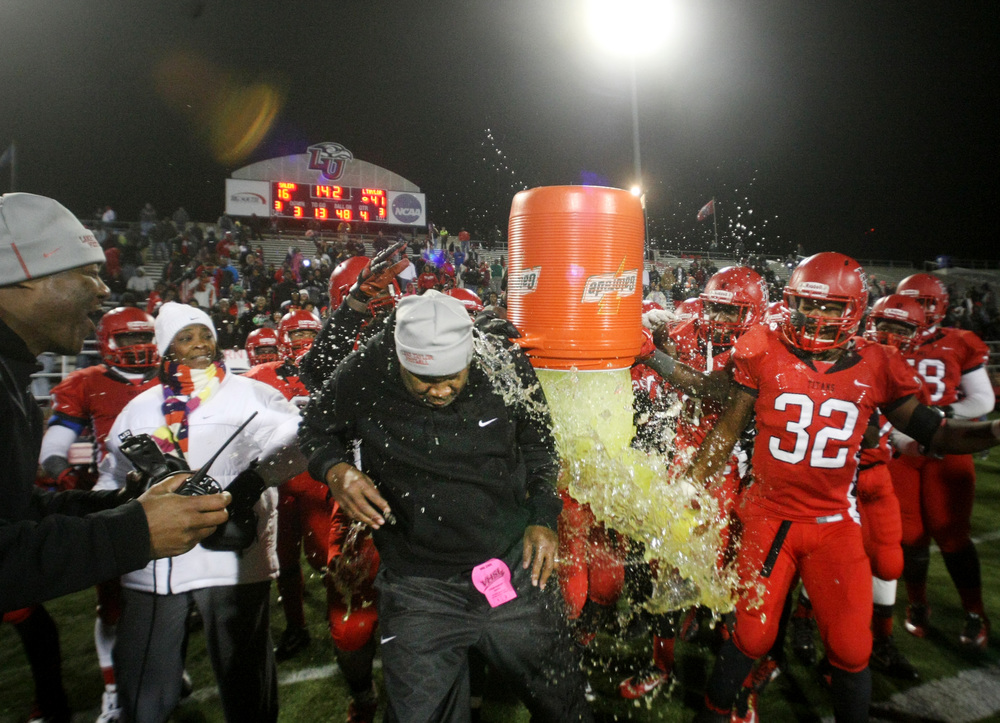Lake Taylor players douse assistant coach David Floyd, center, with gatorade in the closing seconds of their 41-16 win over Salem to claim the Group 4A South championship, Saturday, Dec. 13, 2014 at Williams Field in Lynchburg.  (Jason Hirschfeld | For The Virginian-Pilot