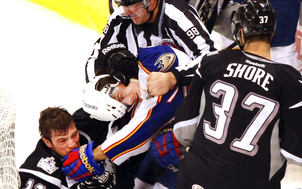 Norfolk's Maxime Sauve, center, is restrained by referee John Grandt after mixing it up with Manchester's Hunter Bishop, left, in a physical first period, Friday, December 19, 2014 at Scope in Norfolk.