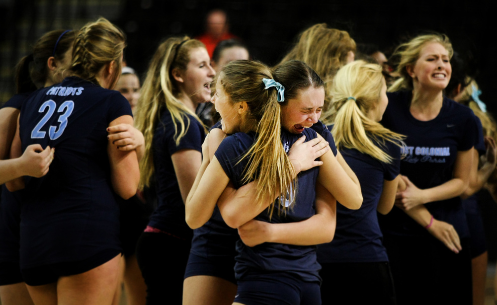 First Colonial's Rowan Ennis, center with face, and teammate Emily Guimond embrace after First Colonial beat James Madison in five-sets to claim the Group 6A girls volleyball championship, Friday, Nov. 21, 2014 at the Siegel Center in Richmond.