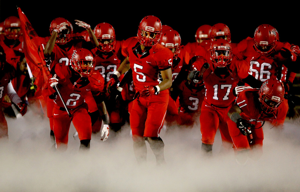 Lake Taylor's Marquis Poole, center, leads the Titans onto the filed prior to the start of their game against Monacan, Friday, Dec. 5, 2014 at Lake Taylor High School in Norfolk. (Jason Hirschfeld | For The Virginian-Pilot)