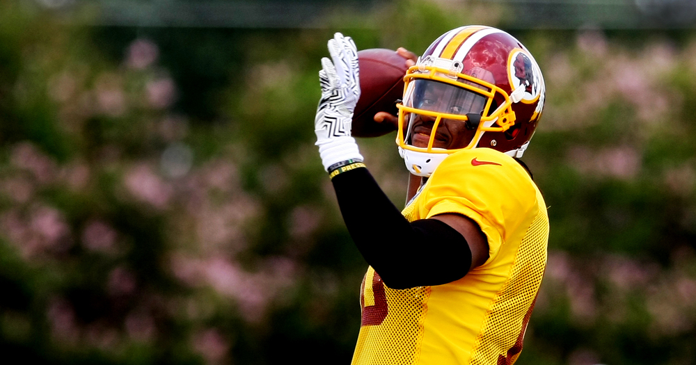 Washington Redskins quarterback Robert Griffin III throws a pass during the team's NFL football training camp in Richmond, Va., Sunday, Aug. 2, 2015.  (AP Photo/Jason Hirschfeld)