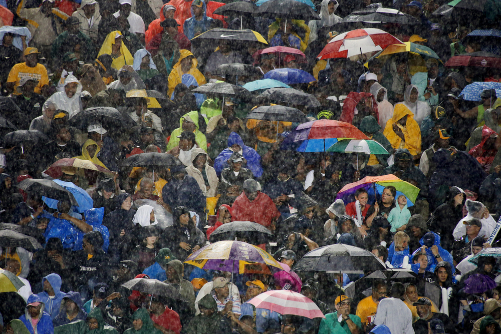 Norfolk State fans use umbrellas to shield themselves from a driving rain while playing ODU, Saturday, Sept. 12, 2015 at Foreman Field in Norfolk.