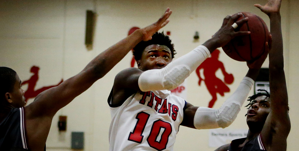 Lake Taylor's JT Wahee slices through Heritage defenders Leland Richardson, left, and Eliezer Rudolph during Lake Taylor's 70-59 win to claim the Group 4A conference championship, Friday, Feb. 26, 2016 at Lake Taylor High School in Norfolk. (Jason Hirschfeld | The Virginian-Pilot)