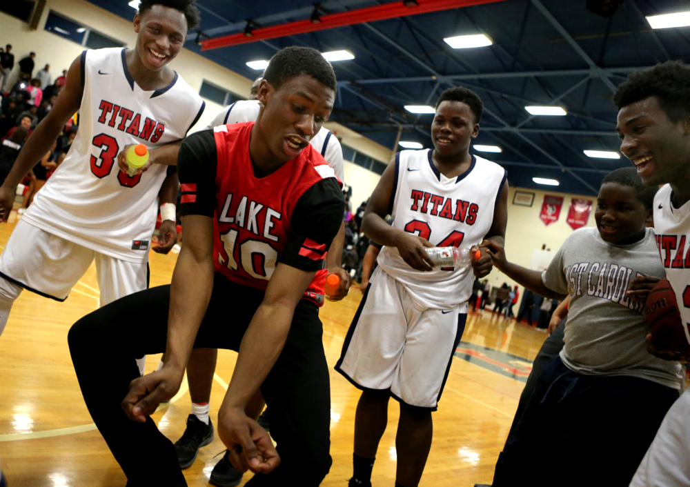 Lake Taylor football player Remono (cq) Newby, center, celebrates with the basketball players after they beat Heritage 70-59 win to claim the Group 4A conference championship, Friday, Feb. 26, 2016 at Lake Taylor High School in Norfolk. (Jason Hirschfeld | The Virginian-Pilot)