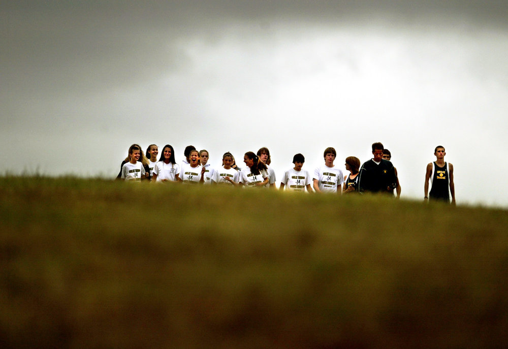 The Great Bridge Cross Country team emerges from the top of a hill before the start of a meet, Tuesday, May 9, 2015 in Chesapeake.