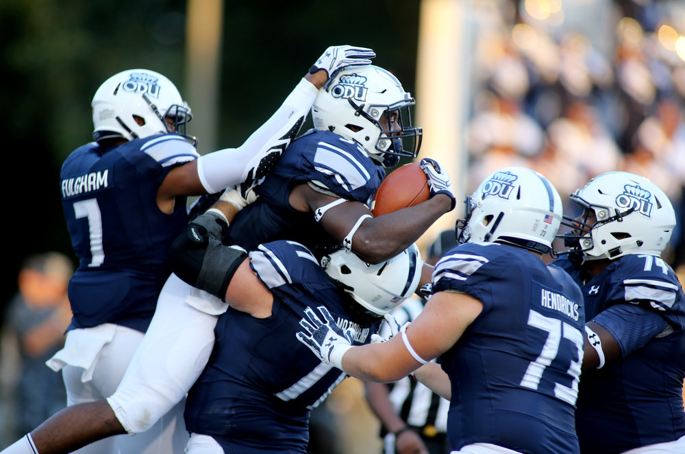 Teammates celebrate with Old Dominion's Jeremy Cox, center with ball, after he scored a fourth quarter touchdown during ODU's 54-21 win, Sunday, Sept. 4, 2016 at Foreman Field in Norfolk.  (Jason Hirschfeld | The Virginian-Pilot)