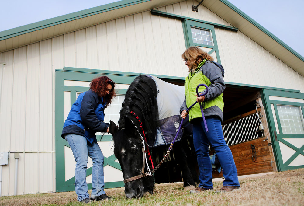 "Roni DeCrescentis, left, and Susan Watkins spend time with ""Sadie"" outside of the barn one final time, Tuesday, Dec. 20, 2016 in Virginia Beach."
