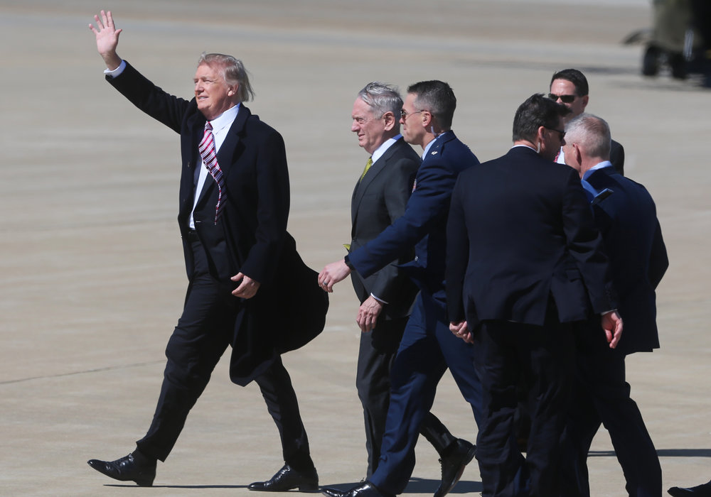 President Donald Trump fights through high winds and waves to a small crowd of supporters upon his arrival alongside Secretary of Defense Gen. James Mattis, Thursday, March 2, 2017 at Langley Air Force Base in Hampton, Va.