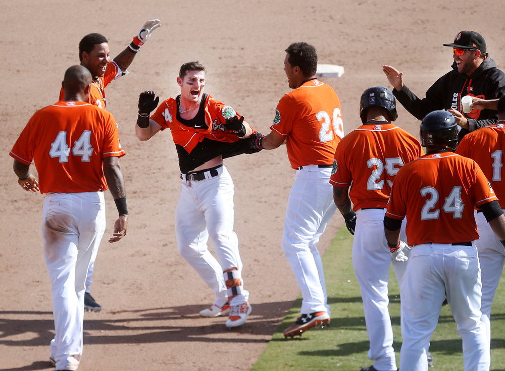 Tides teammates celebrate with Johnny Giavotella after he hit a walk-off two-run triple to beat Charlotte in the rubber match of their series, Sunday, April 16, 2017 at Harbor Park in Norfolk.
