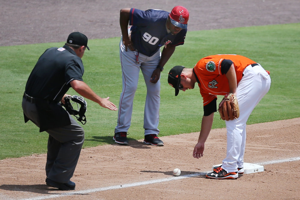 Tides third baseman Chris Johnson, right, home plate umpire Jerry Riggs, left, and Louisville manager Delino Deshields watch as the ball slowly rolls foul during the Tides' 3-1 win, Thursday, June 29, 2017 at Harbor Park in Norfolk.