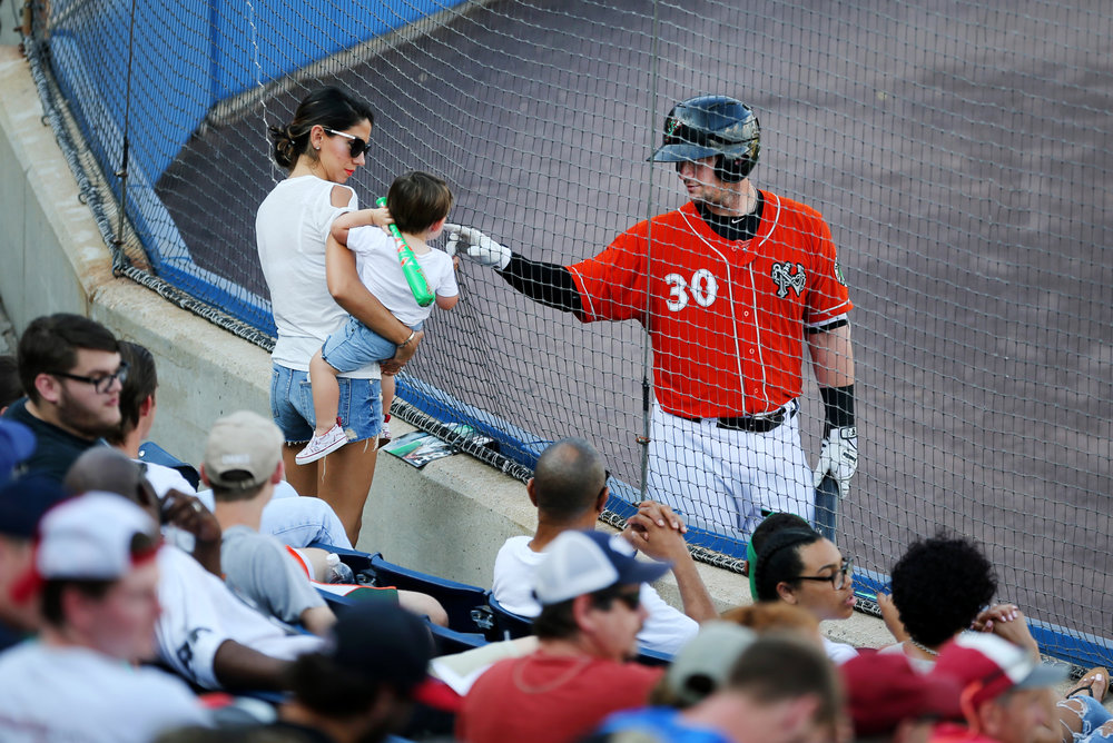 While on-deck, Norfolk's Chris Johnson greets his 18-month-old son Greyson and wife Tia in a 6-1 loss to Durham, Sunday, July 2, 2017 at Harbor Park in Norfolk.