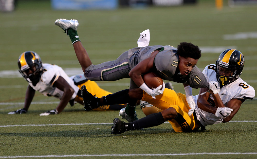 Bishop Sullivan's Bennie Merritt loses his helmet while being tackled by American Heritage's Tyson Campbell during the Crusaders' 14-7 loss, Saturday, August 26, 2017 at the Sportsplex in Virginia Beach.