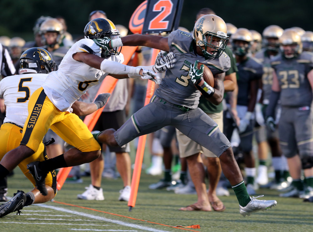 Bishop Sullivan's Mike Martinez is pushed out of bounds by American Heritage's Dyllon (cq) Lester during the Crusaders' 14-7 loss, Saturday, August 26, 2017 at the Sportsplex in Virginia Beach.