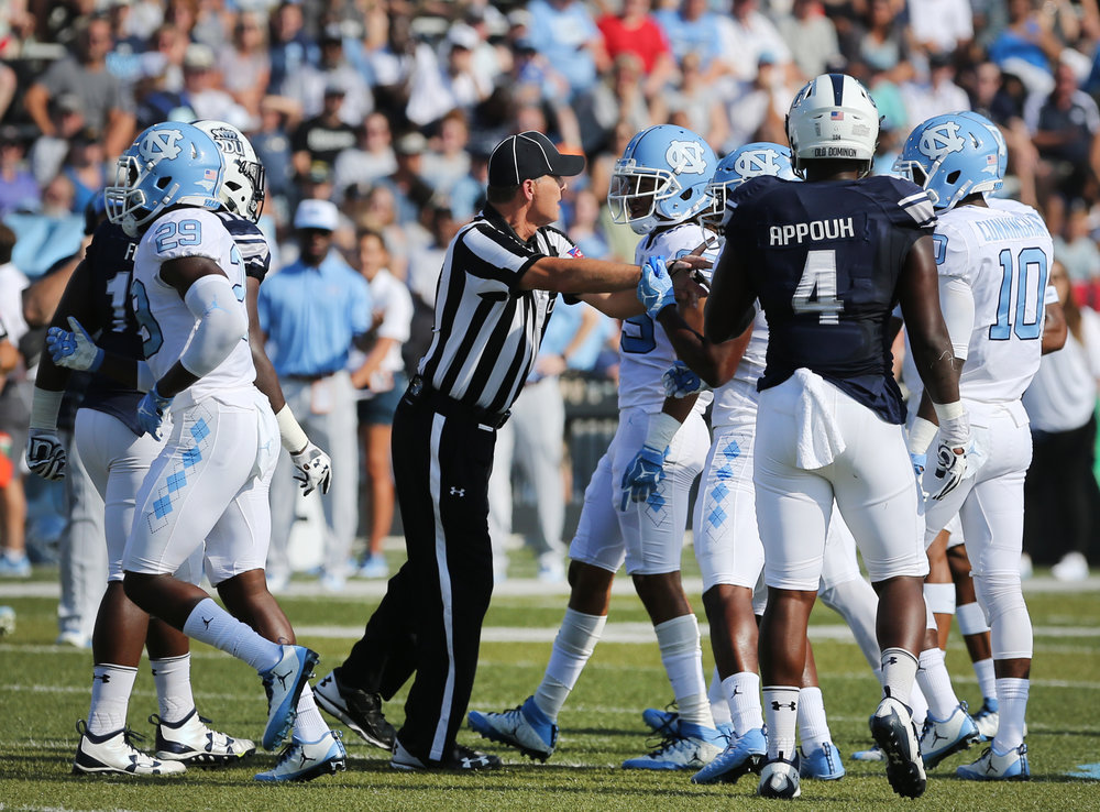 An official separates UNC and Old Dominion players after a skirmish in the second half football game, Saturday, Sept. 16, 2017 in Norfolk, Va.