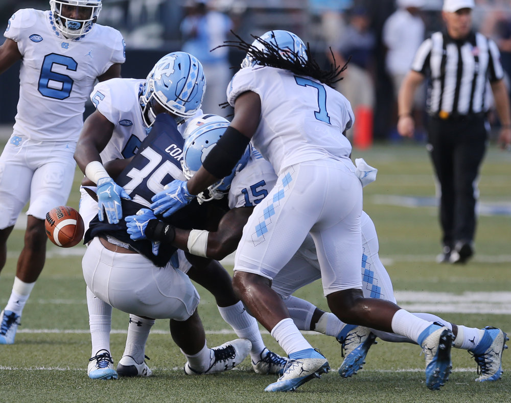 UNC defenders Patrice Rene (5), Donnie Miles (15) and Jonathan Smith force a fumble by Old Dominion's Jeremy Cox (35) in the second half of an NCAA college football game, Saturday, Sept. 16, 2017 in Norfolk, Va.