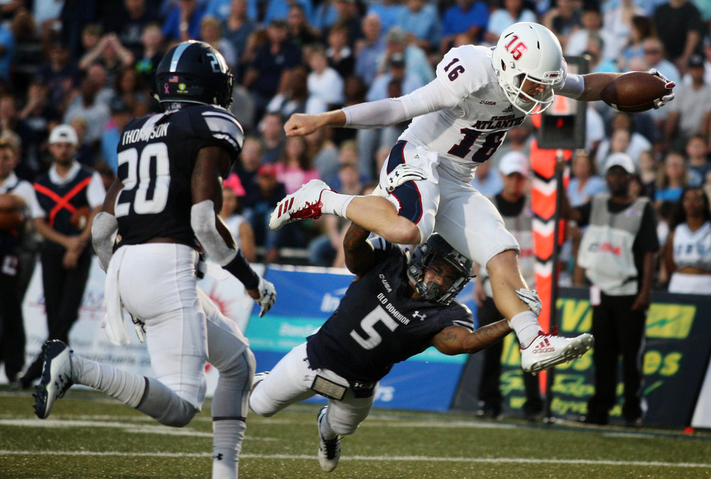 Florida Atlantic quarterback Jason Driskel hurdles Old Dominion's James Brickhouse for a touchdown as ODU's Rob Thompson closes in , Saturday, Oct. 7, 2017 at Foreman Field in Norfolk.