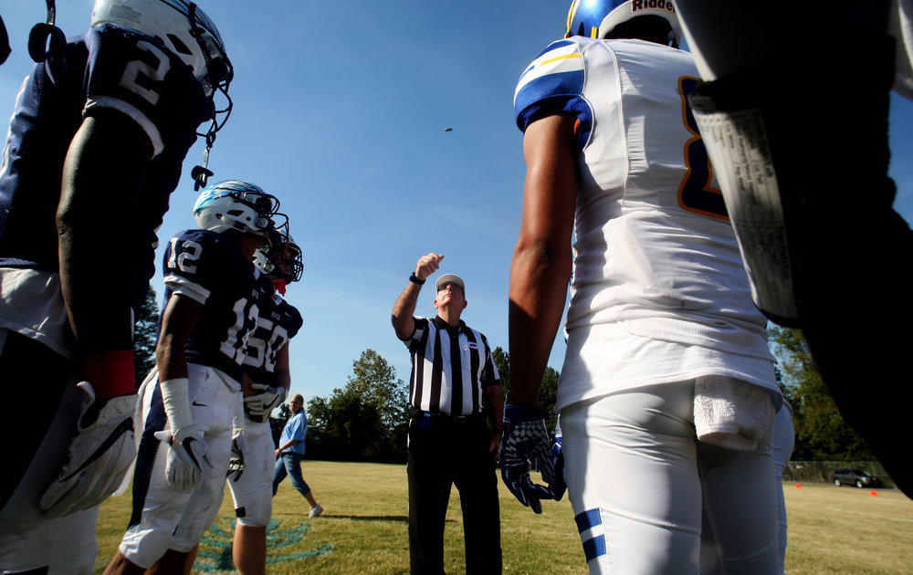 The head referee performs the coin toss before the start of the Tigers' 35-14 win over Indian River, Saturday, Oct. 21, 2017 at Indian River High School in Chesapeake.