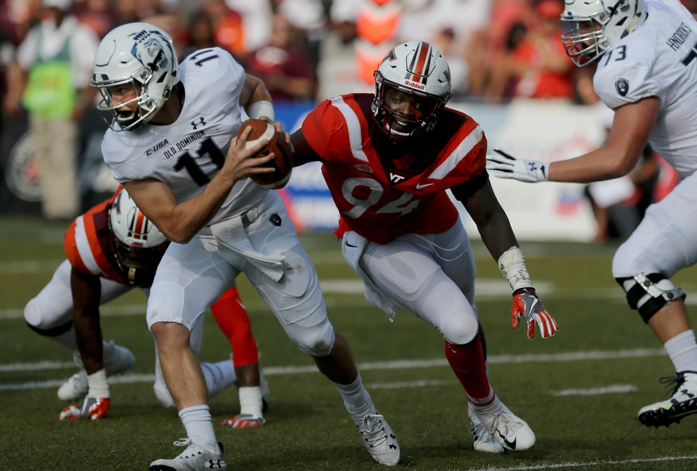 Old Dominion quarterback Blake LaRussa is flushed out of the by Virginia Tech's Trevon Hill during the second half of an NCAA college football game, Saturday, Sept. 22, 2018, in Norfolk, Va. Old Dominion won 49-35. (AP Photo/Jason Hirschfeld)