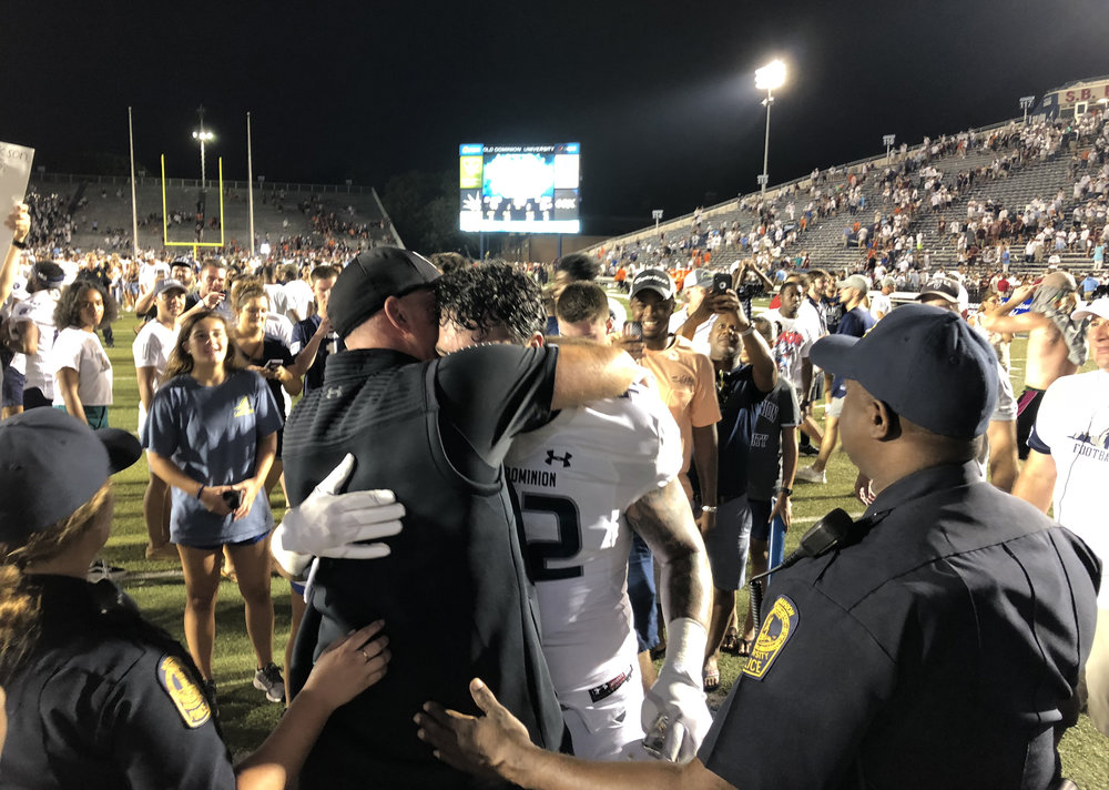 Old Dominion head football coach Bobby Wilder embraces his son Derek Wilder after an NCAA college football game Saturday, Sept. 22, 2018, in Norfolk, Va. Old Dominion won 49-35. (AP Photo/Jason Hirschfeld)