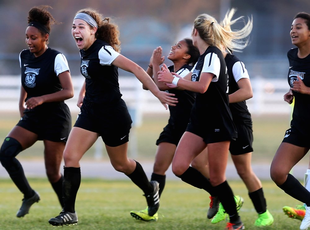 As a teammate celebrates skyward, an excited Landstown's Trinity Sudderth celebrates after her goal tied the match 1-1 in the closing seconds of their draw against Cox, Tuesday, March 21, 2017 at Cox high School in Virginia Beach.