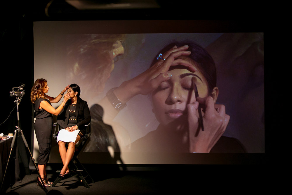 Karuna applying makeup to the model. A close-up image is projected on the theater screen for the audience to see the fine details. Photo by Tara Sharma Photography.