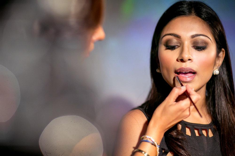 Close-up of Karuna applying makeup to the model. Photo by Tara Sharma Photography.