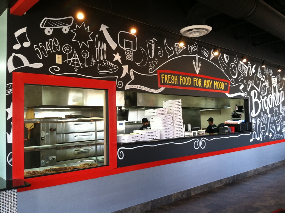An image of the interior of Slim's restaurant, featuring a look at the kitchen and illustrative, hand-drawn mural designed by Kazoo.