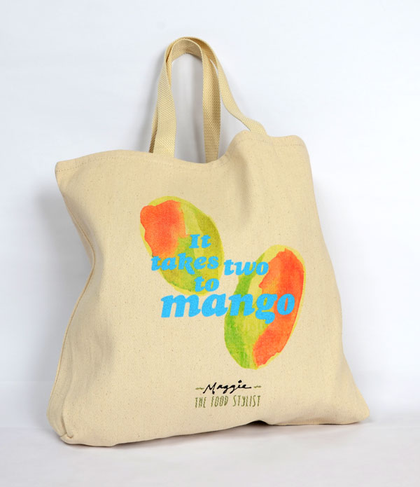 "Hand painted mango design with the words ""It takes two to mango"" on a canvas tote bag. Graphic design, promotional material."