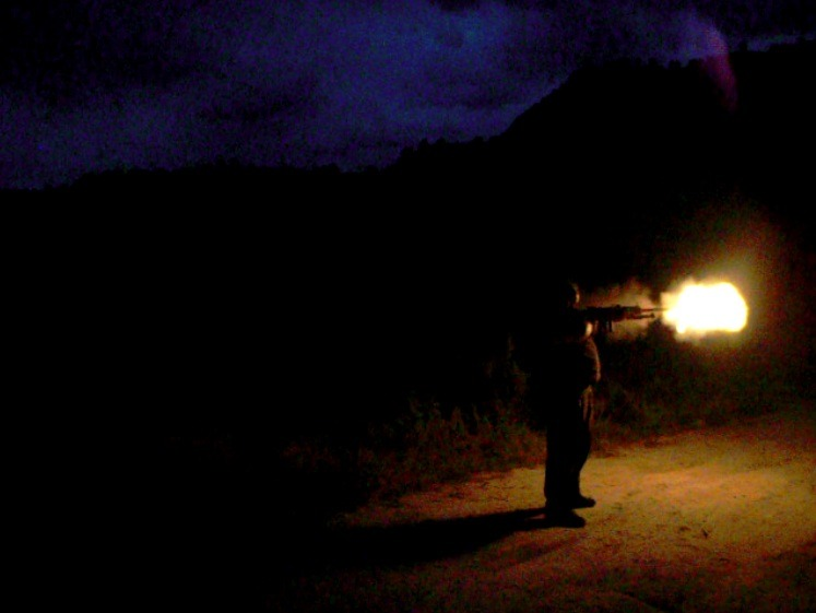 Screen shot taken from a video of me shooting a .50 Caliber sniper rifle in the dark. (It looks much darker in the video than it really was. I could actually see where I was shooting…somewhat! I had a hard time just holding the damn thing up it was so heavy though!)