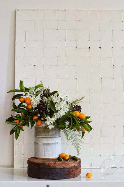 Tiny orange kumquats combined with paperwhites, dark berries of English ivy and lacy ferns
