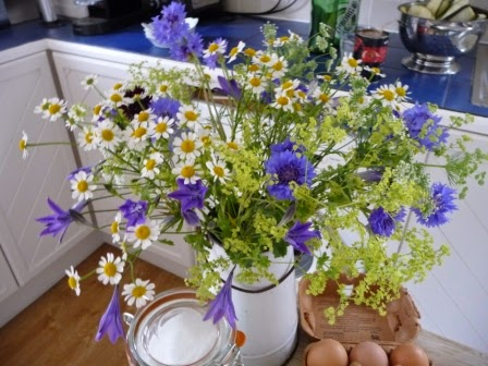 Pretty container of country-style flowers atop the butcher's block