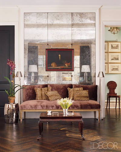 In this living room a wall of antique mirrored mercury-glass panels serves as a backdrop for the seating area as well as for the painting.