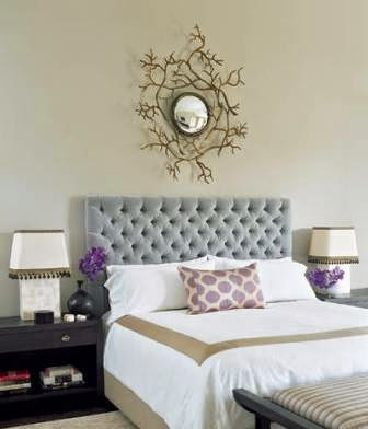 A bronze mirror serves as a reflective work of art in the bedroom below.