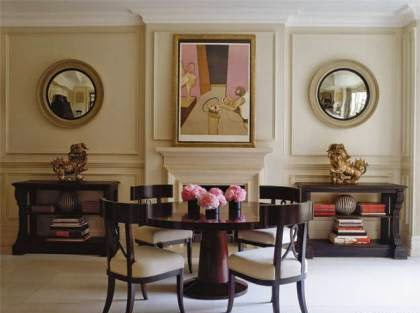 Two convex mirrors flank the fireplace in the dining hall below emphasising the room's symmetry and play off the circular shape of the mahogany dining table. A Francis Bacon print is displayed over the mantel piece.