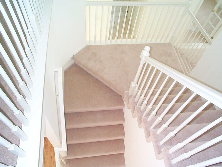 A sense of light and space created by the white painted balusters and bannisters and light coloured carpet.