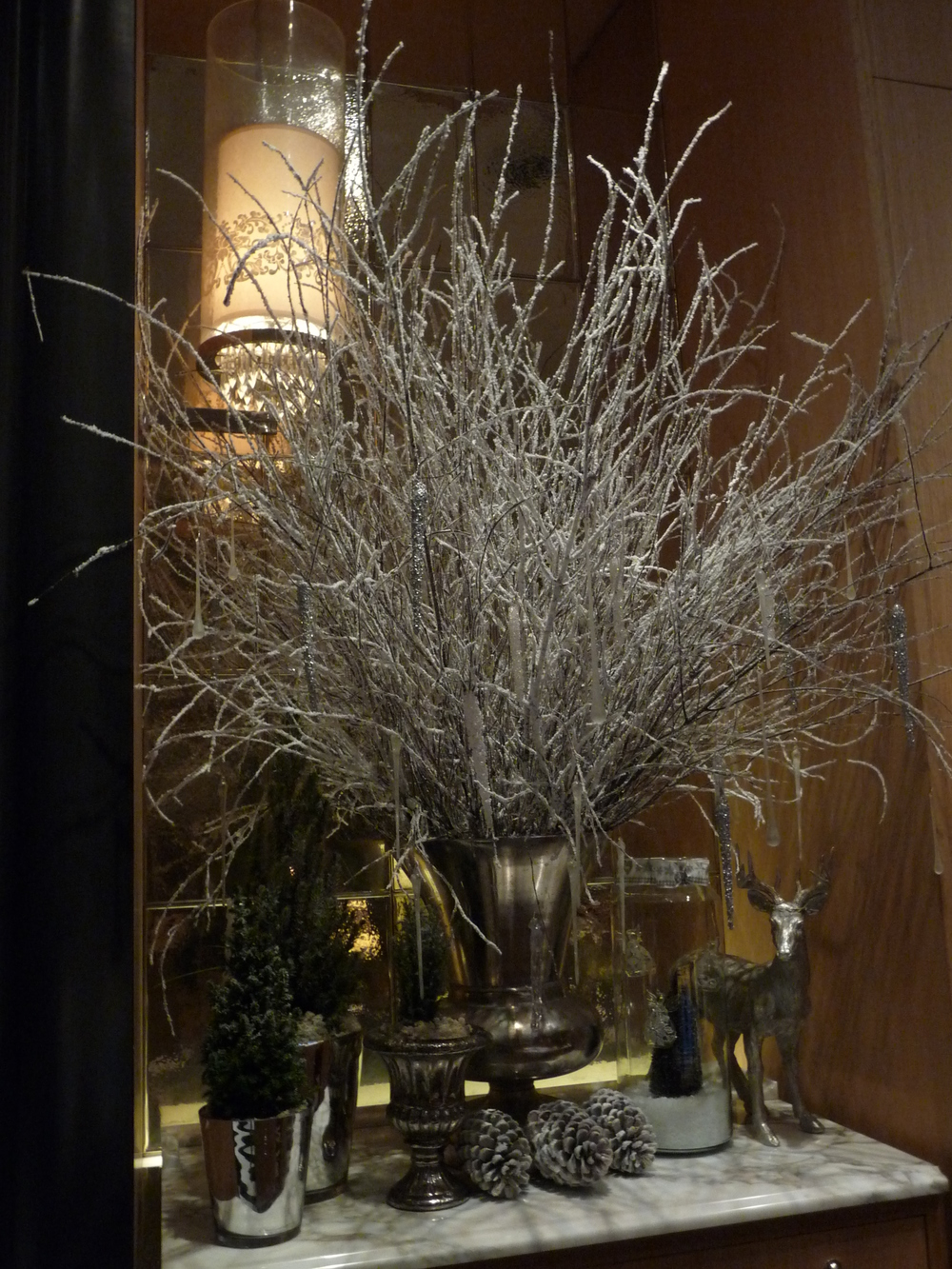 Beautiful Christmas arrangements of natural twigs sprayed white with decorations hanging from them