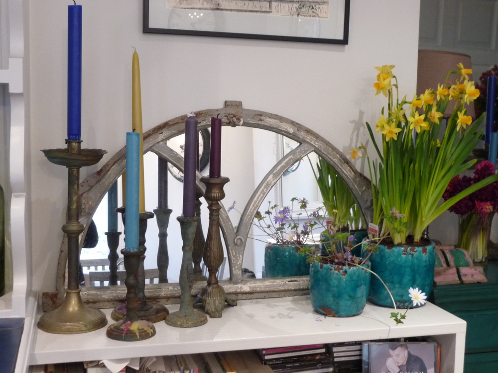 More pots of miniature daffodils and a delicate mauve flowering plant on the bookcase in the kitchen with five candlesticks with different spring coloured candles