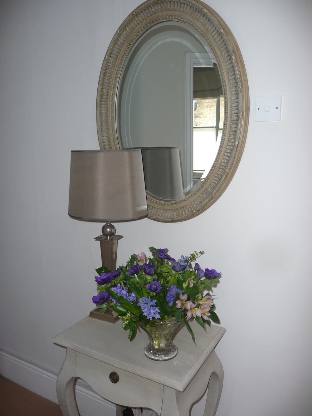 This mirror is made from bamboo and sits in the hall. I have created a focal point with the table, light and flowers