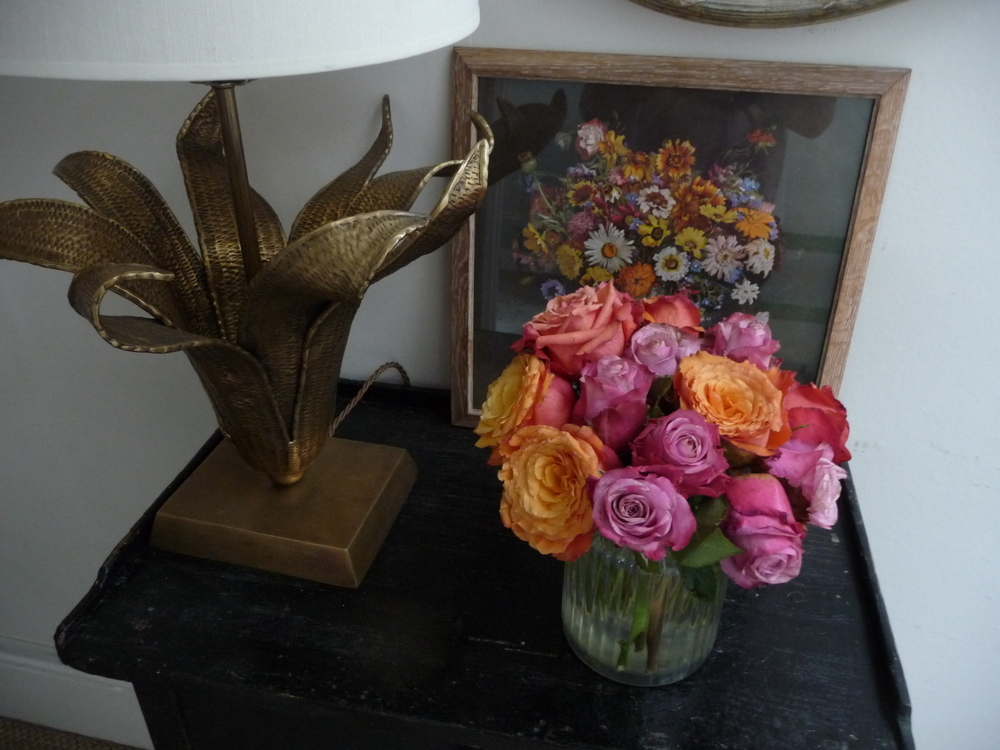 In my hall I have this vase of pink and orange roses which I've cut very short and crammed into this glass jar/vase.  Roses last much longer if cut very short. I chose these two colours to complement the 60s flower print that sits behind.