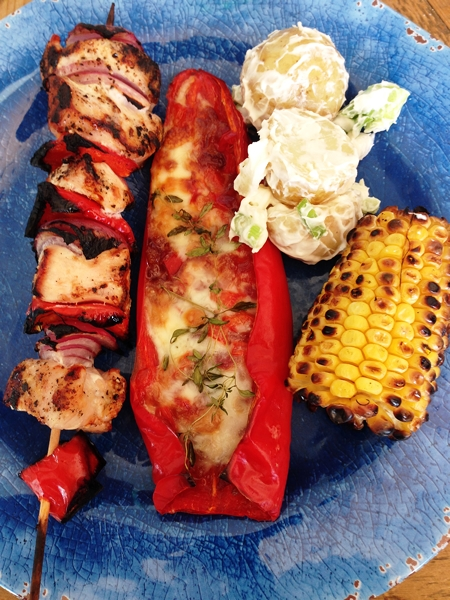 A main course of chicken breast skewers and sweet corn on the barbecue, stuffed peppers with taleggio and a potato salad