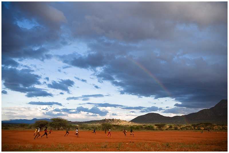 As the children from the school play soccer on the dirt field, a rainbow shines over the field, a sign of hope for a brighter future despite the hardships and challenges facing these children.