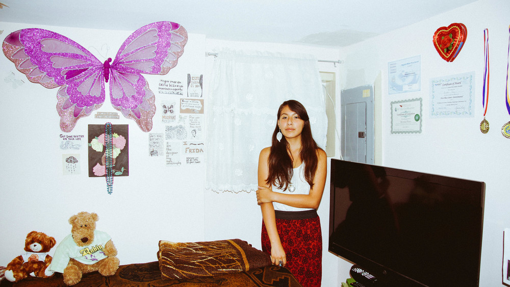 BRENDA PEREZ  in the bedroom she shares with her mother. Her numerous academic accomplishments adorn the walls.  The large purple monarch is a symbol of the immigration reform movement.