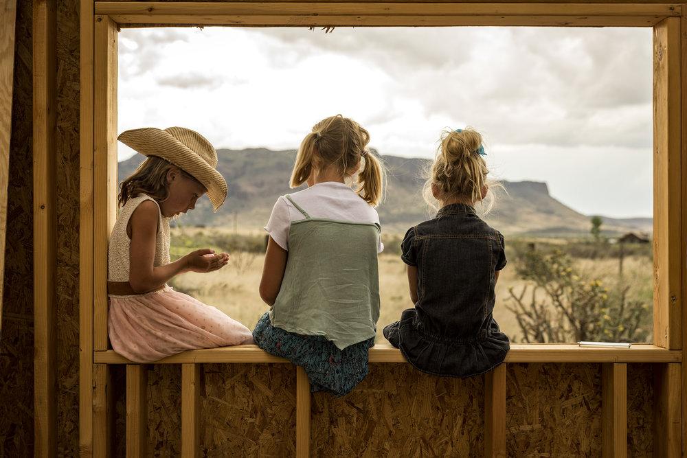 Girls in Window of Framed House