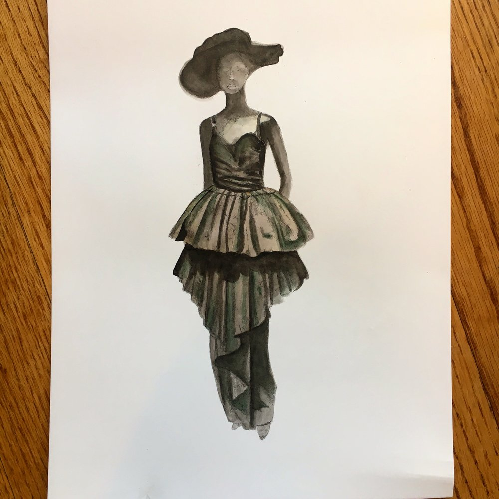 A series of dramatically displayed black dresses represented flowers and stems. This one was a flower while there were very fitted straight skirts representing the stems.