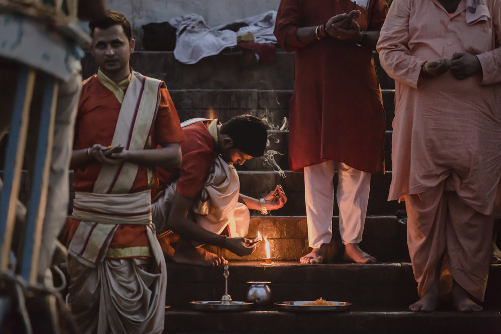 A Pandits (Hindu priest) lights a small Diya in preparation for the Ganga Aarti.