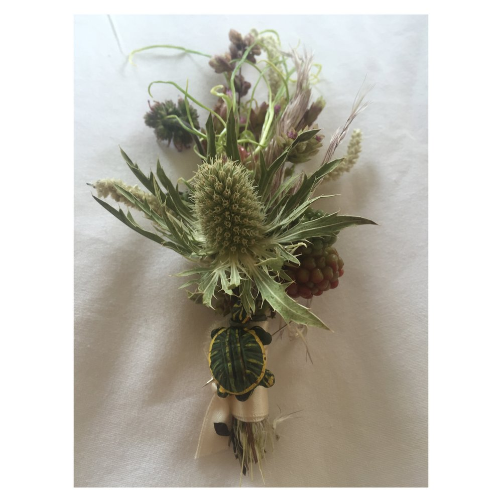 BOUTONNIERE WITH TURTLE FIGURINE TO RESEMBLE THEIR PET TURTLE
