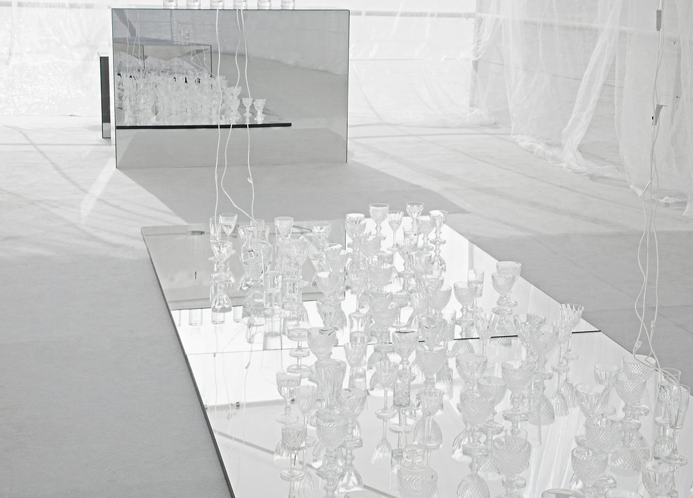 """""""WATERNESS""""  CTRLZAK Studio and JCP present water as a sensual element, life as the origin and womb of all things. Playing with transparency and reflection, water is a mirage that fuses art and design in an alchemical way.  """"To look, listen and sample are just some of the actions implemented through Waterness, a path of personal awareness and reconsideration of the value of water and our direct relationship with this.""""  - CTRLZAK  The installation """"Dolmlod"""" in the middle of the room is a table designed for JCP, displaying a multitude of glasses and decanters made of borosilicate glass of different sizes filled with water that drips from the ceiling. Waterness is completed with a tasting of different types of water."""
