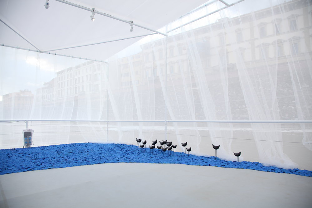 """""""MIGRATION""""  Bitossi Ceramiche and Alessio Sarri present a metaphorical ceramic installation dedicated to the sea where, on the surface of the water, birds migrate to new and luminous shores.  Whether speaking about the movement of a single person or a group, as individuals or a flock, movement caused by nature or social factors, the decision to leave a place to reach another always has more than one reason, generating a complex and controversial phenomenon.  The possibility to be reinvented is the way of man when creating a new habitat capable of welcome. Aldo Londi, artistic director of Bitossi Ceramiche for over four decades, creates a expressive language made up of matter and form painted in an unmistakable color: blue. Here he presents the """"Birds"""" series, in creation since 1955."""