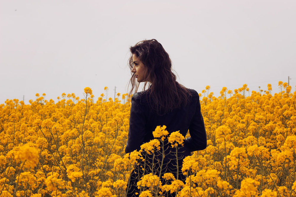 Model in a field of yellow flowers