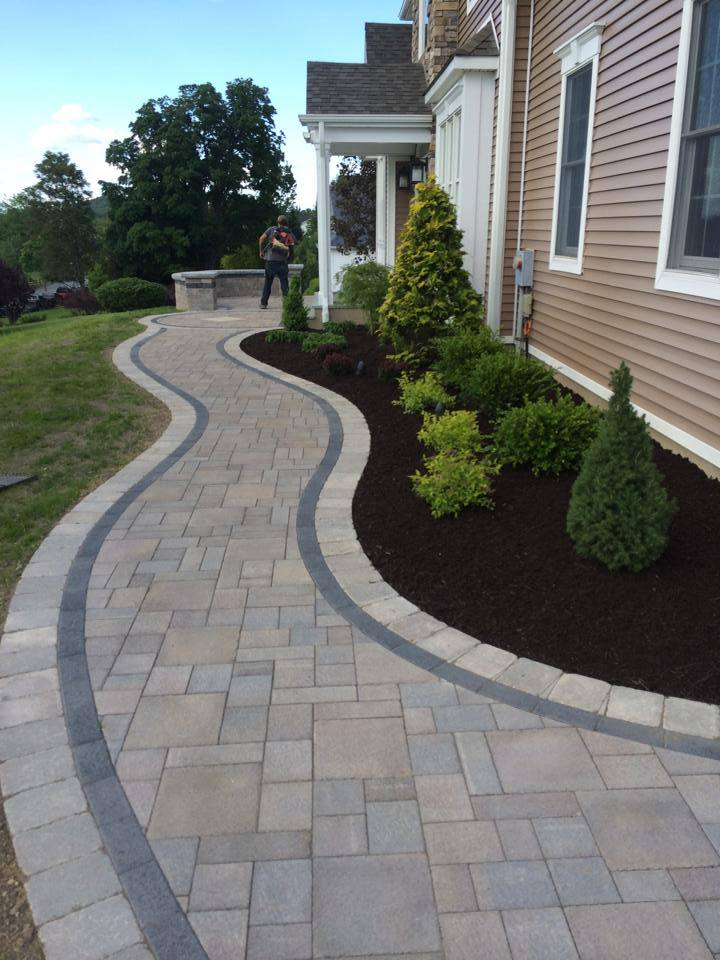 The Landworx team putting the finishing touches on a sweeping, graceful front entrance built using Unilock products.